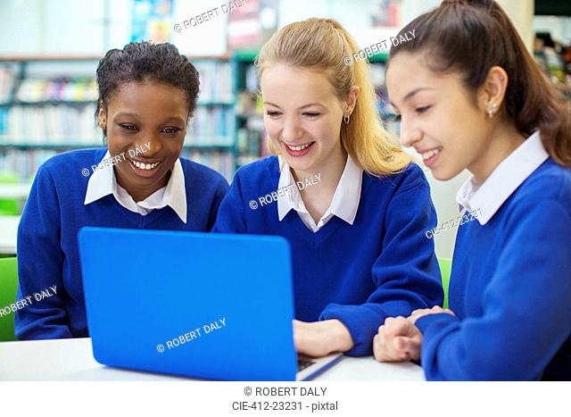 Three smiling female students wearing blue school uniforms working on laptop in library