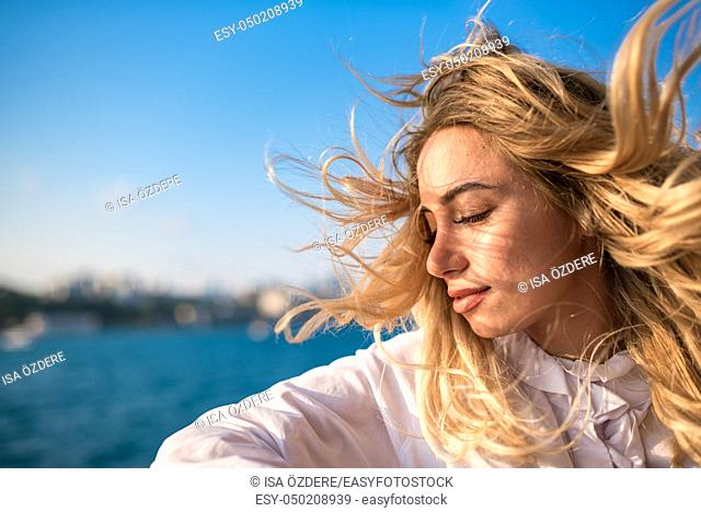 Attractive young beautiful girl enjoys moment while cruising with view of sea on background. Lifestyle concept