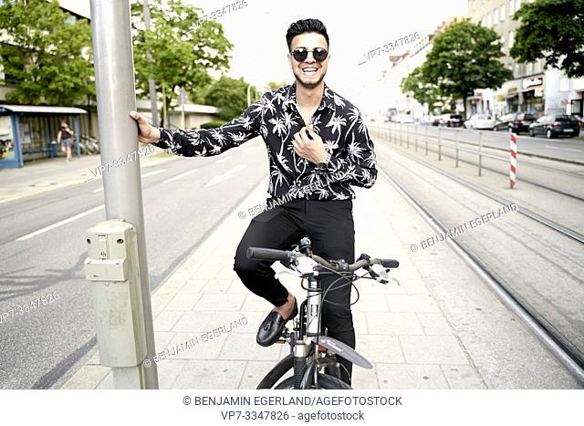 young Afghan man smiling on bike in city Munich, Germany