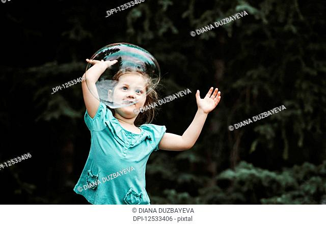 Young girl chases a large bubble floating in the air; Alberta, Canada