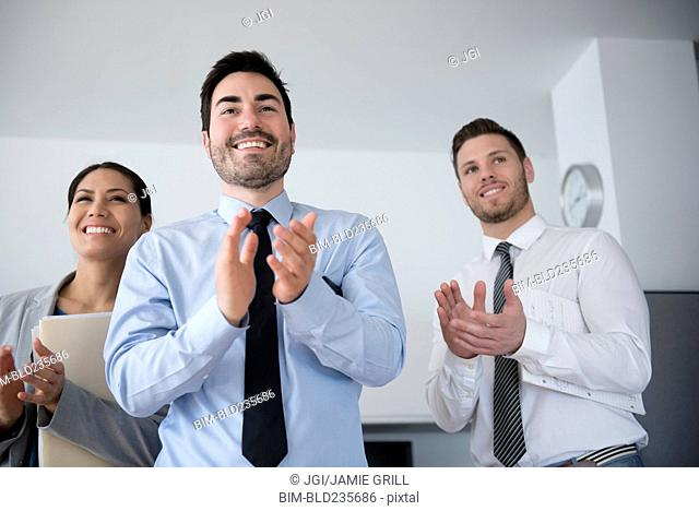 Business people applauding in office meeting
