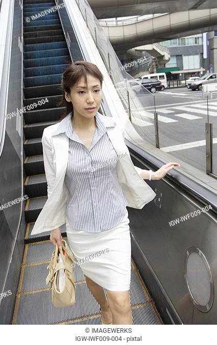 A woman walking ahead after descending from the escalators