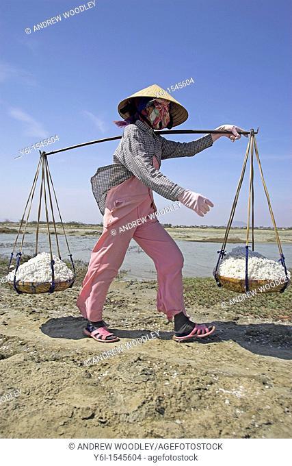 Woman in conical hat carries wicker pannier baskets of salt along dyke between salt ponds Phan Thiet Vietnam