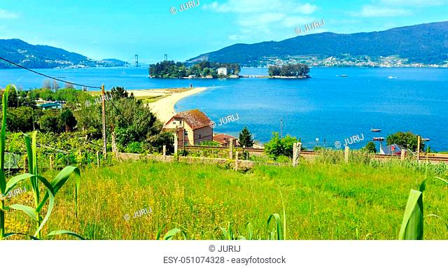Sandy beach in Cesantes town and San Simon island (Galicia, Spain). Summer Ria de Vigo landscape