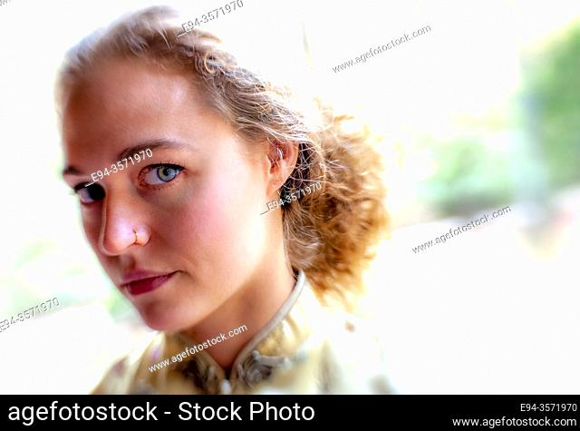 A 28 year old blond woman looking at the camera