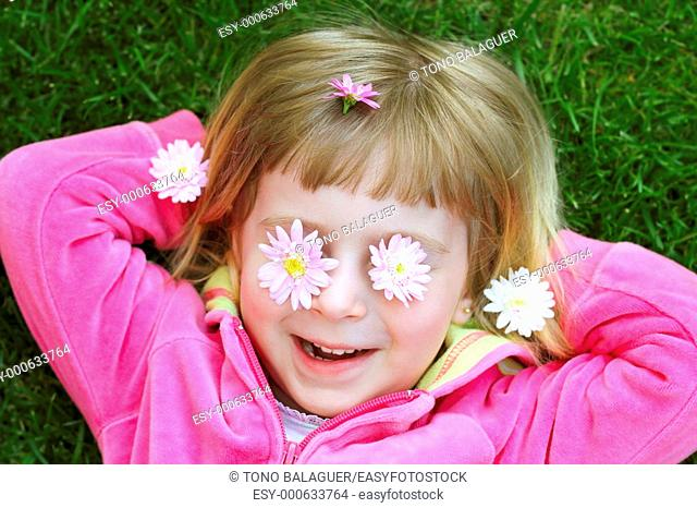 little girl laying grass daisy flowers in eyes