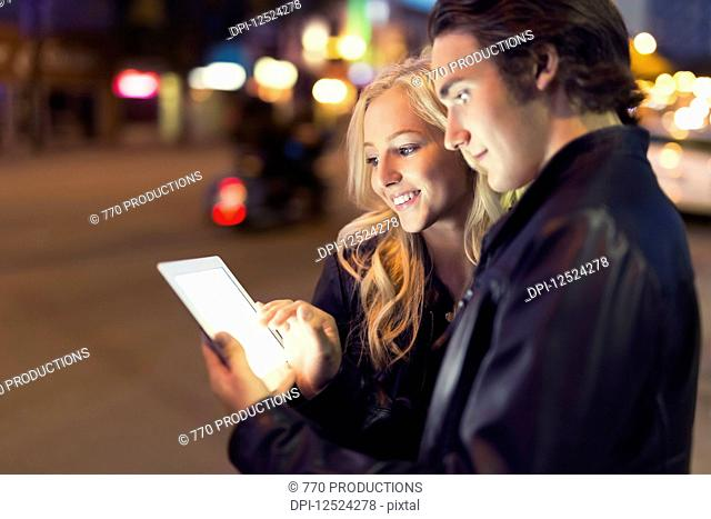 A young couple use a tablet along a street at dusk with the glowing screen illuminating their faces; Edmonton, Alberta, Canada