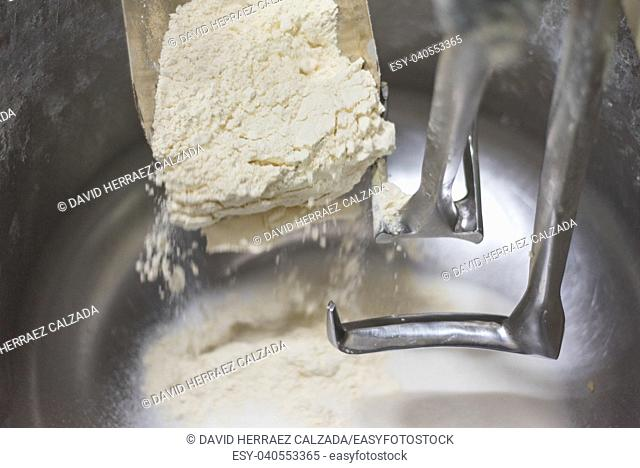 Loading flour into an industrial dough mixer. Close up view