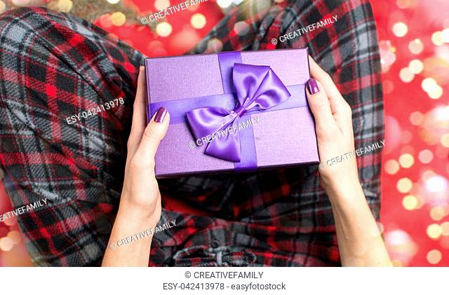 female holding a purple Christmas present