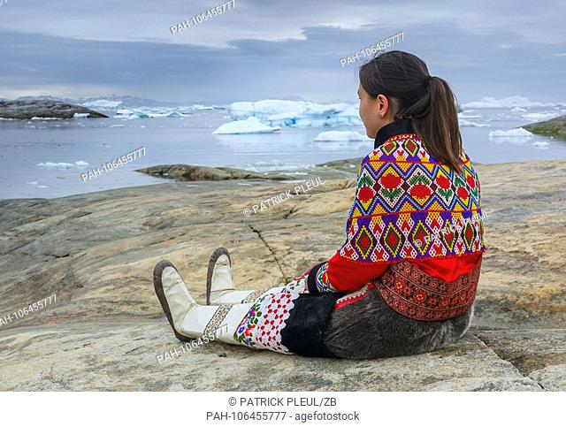 21.06.2018, Gronland, Denmark: A young woman in national costume on July 21st is sitting on a rock in the coastal town of Ilulissat in western Greenland