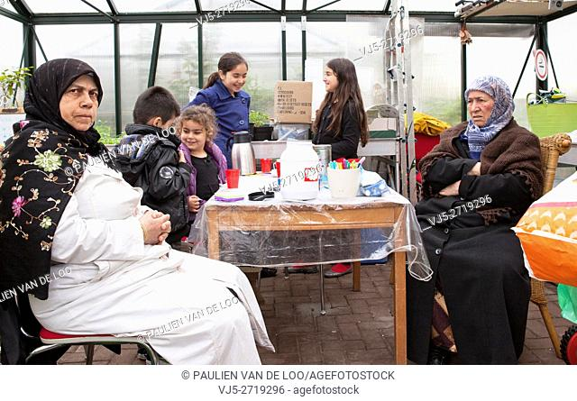 Rotterdam, Netherlands, Muslim women with children shelter from the rain in a greenhouse