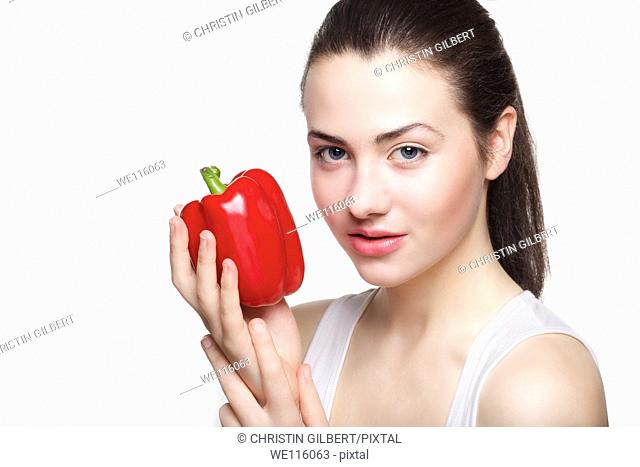 Young beautiful Caucasian woman smiling while holding red bell pepper