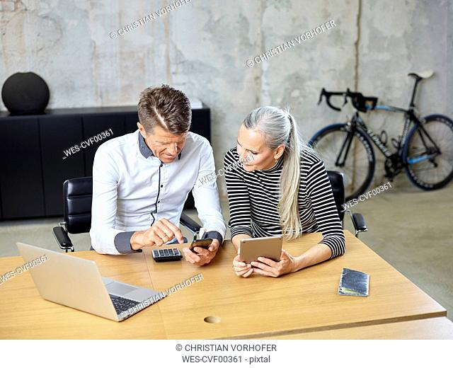 Businessman and businesswoman with cell phone and tablet in office