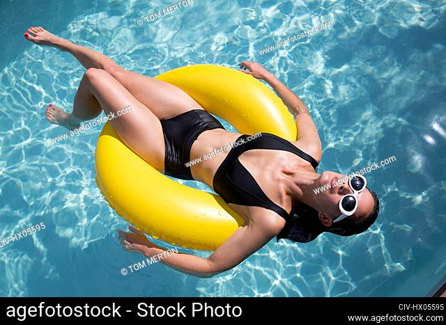 Sensual woman in black bikini floating on inflatable ring in sunny summer swimming pool