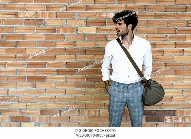 Young man with bag standing at brick wall looking around