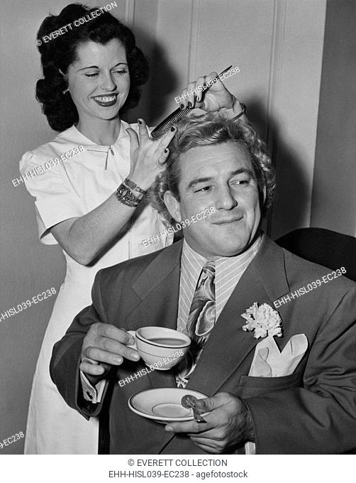Wrestler Gorgeous George holding a tea cup as his hair is styled by Miss Bettie of Hollywood. Feb. 19, 1949. He appeared in the 1949 movie, ALIAS THE CHAMP