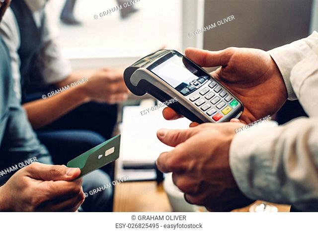 Close up of a card payment being made betweem a man and a waiter in a cafe