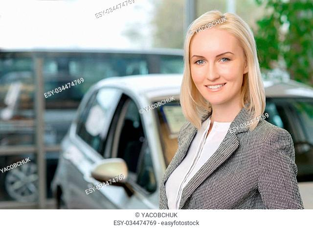 In the car salon. Nice-looking young woman is smiling pleasantly while posing in front of a car