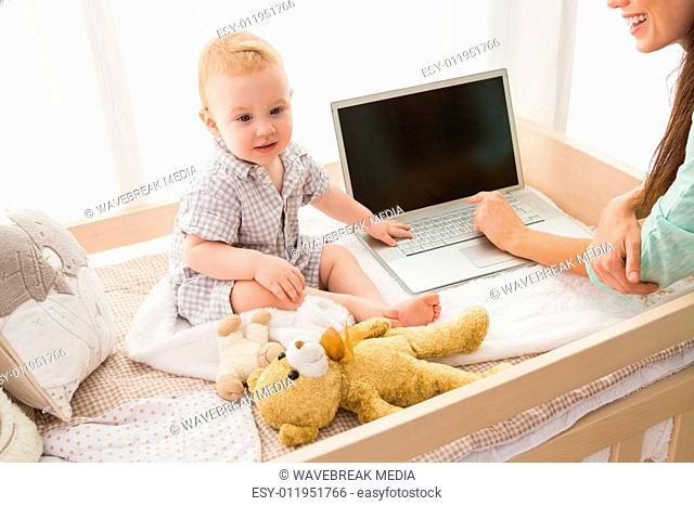Happy mother using laptop with her baby boy