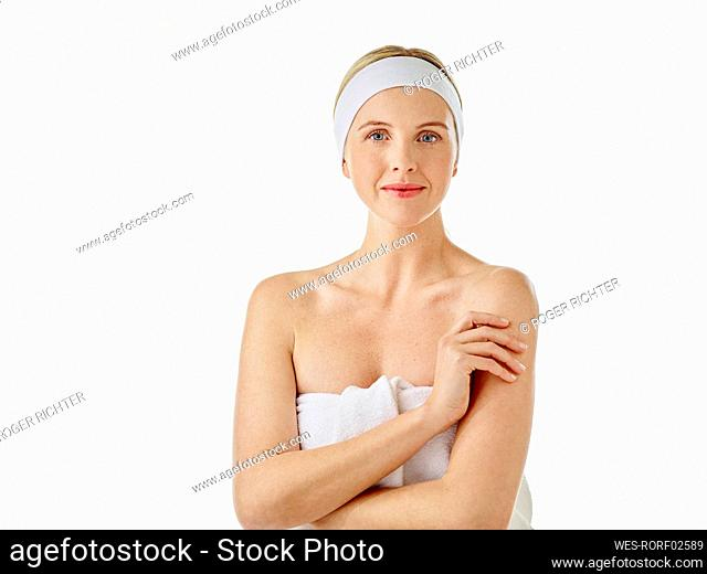 Young woman with headband wrapped in towel staring while standing against white background