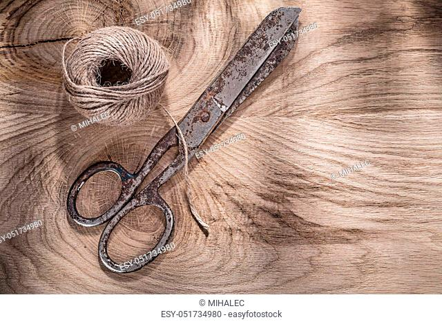 Skein of rope vintage scissors on wooden board