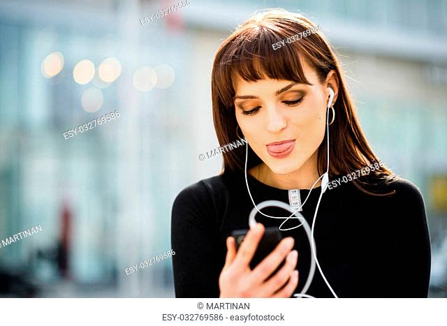Young woman sticking out tongue while making video call in street