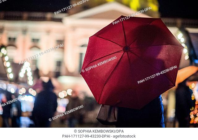 A woman walks with an umbrella over the grounds of the Christmas market in front of Charlottenburg Palace in Berlin, Germany, 27 November 2017