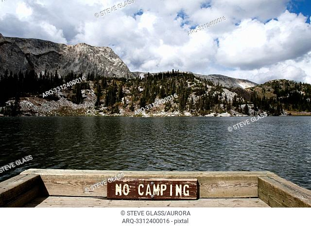 A sign reading No camping sits on a fence above an alpine lake, Mirror Lake, in the Snowy Range, Wyoming