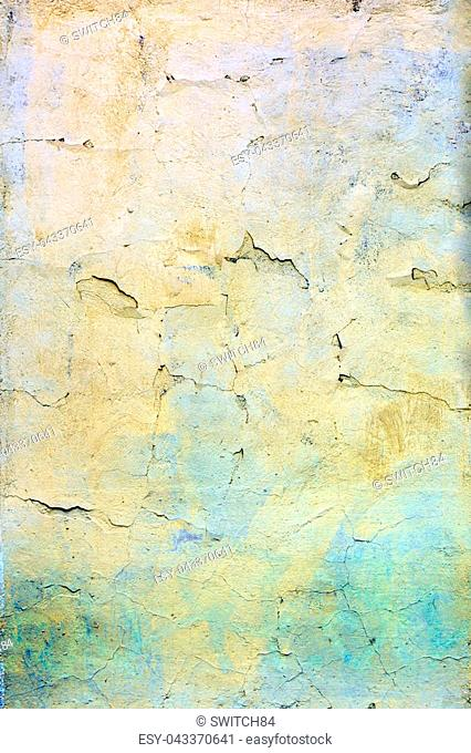 A wall with cracked yellow and blue paint. Beautiful bright background. Texture of old cover with cracks