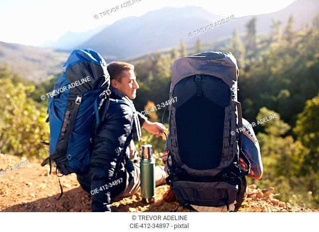 Young couple with backpacks hiking, taking a coffee break