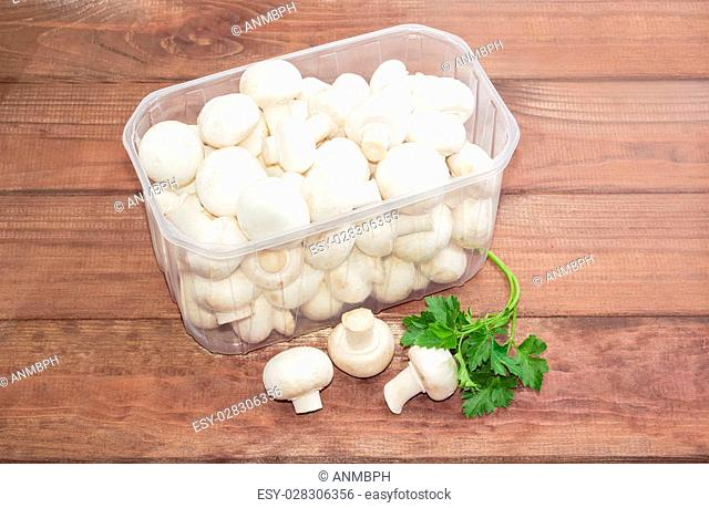 Fresh uncooked button mushrooms in a transparent plastic tray, several mushrooms separately and a sprig of parsley on a dark wooden surface