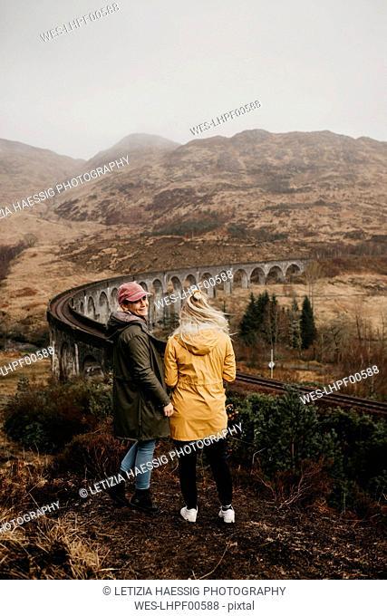 UK, Scotland, Highland, Glenfinnan Viaduct, female friends looking at view