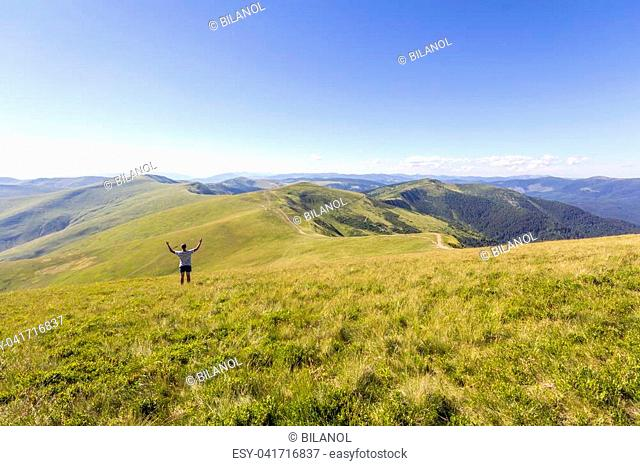Lonely hiker standing in mountains. Tourist man enjoy mountain view
