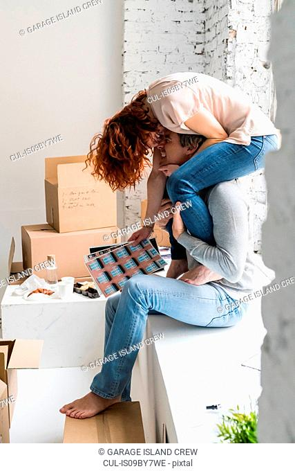 Romantic couple moving into industrial style apartment, woman sitting on boyfriend's shoulders holding photographs