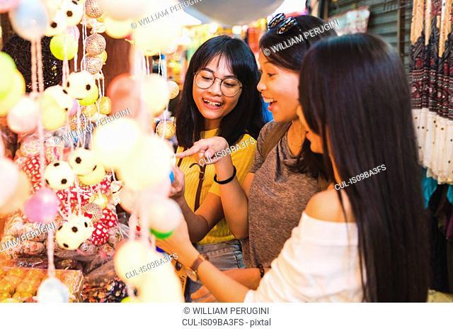Tourists admiring decorative lights in bazaar, Bangkok, Thailand