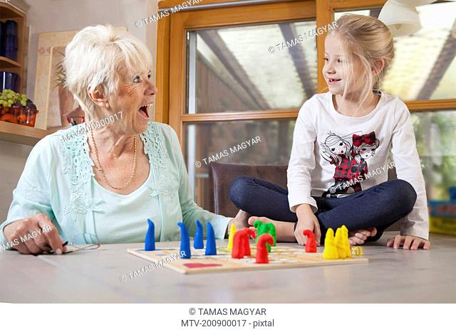Girl playing board game with her grandmother, Bavaria, Germany
