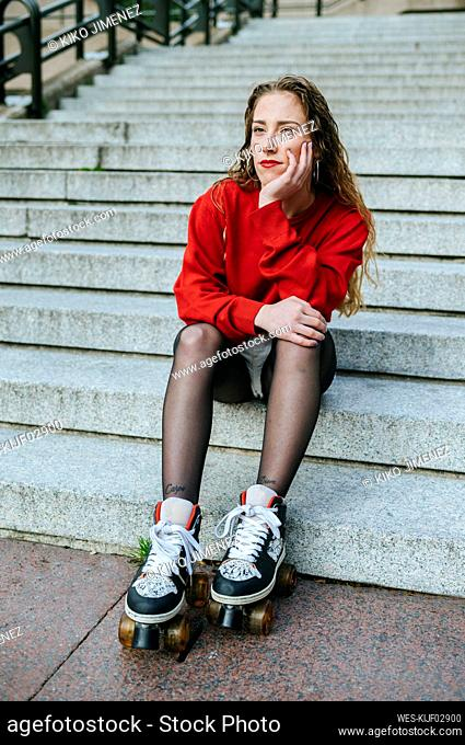 Young woman with roller skates sitting on stairs