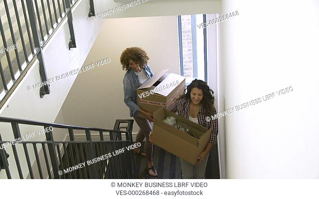 Two Women carrying boxes up stairs as they move into new home.Shot on Sony FS700 in PAL format at a frame rate of 25fps