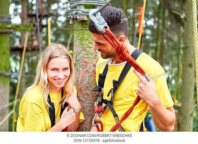 Glückliches junges Paar im Hochseilgarten bei einem Teambuilding Event