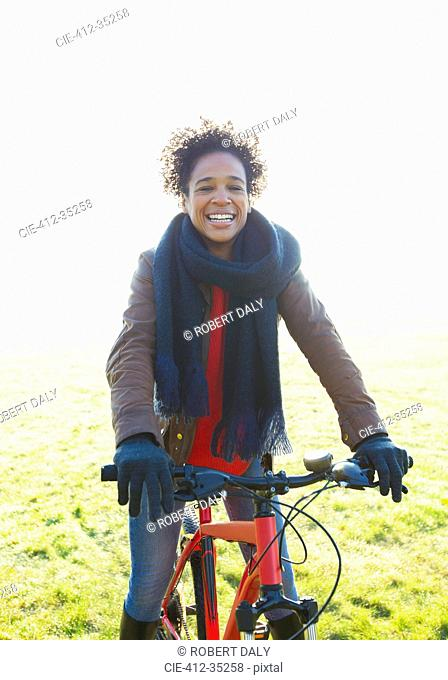 Portrait smiling woman bike riding in sunny park grass