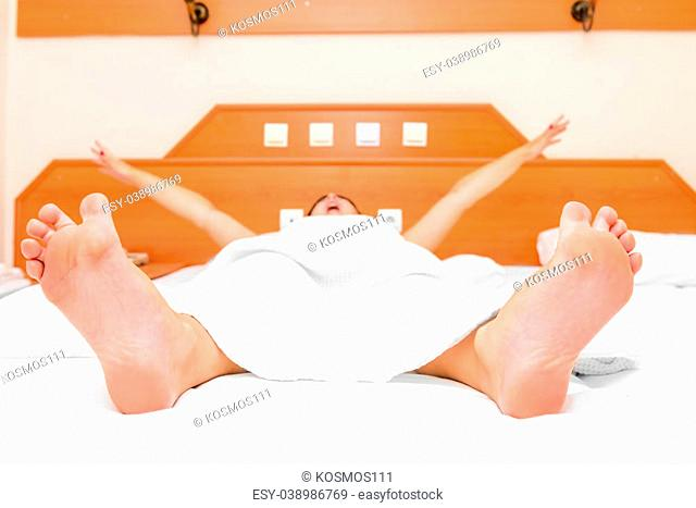 young girl lying in bed yawning and stretching