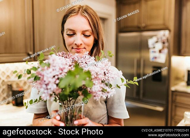Smiling woman smells fresh cut lilacs in her kitchen