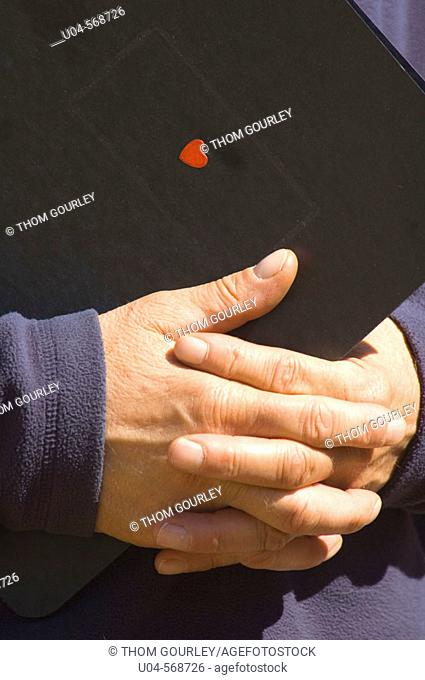 Detail of man's hands holding a binder with a tiny heart sticker