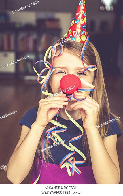 Little girl with clown's nose and cap blowing streamer