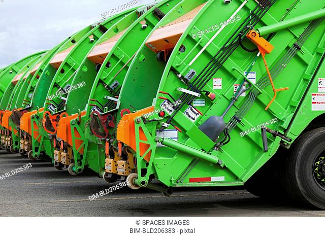 Green garbage trucks in a row