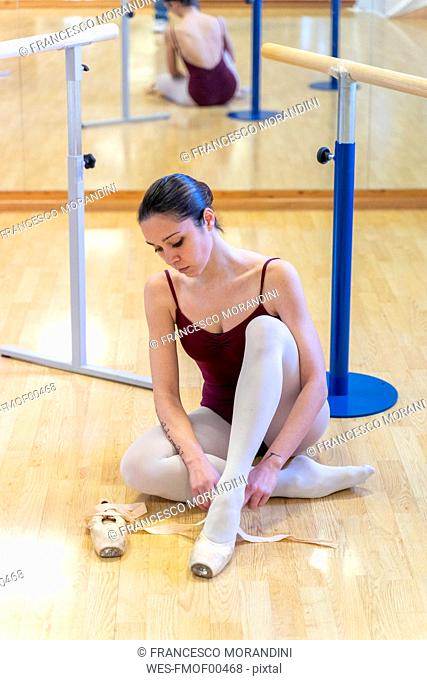 Ballet dancer putting on shoes