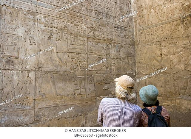Two tourists looking at the hieroglyphs in the Amun Temple, Luxor Temple, Luxor, Nile Valley, Egypt, Africa