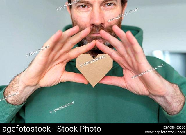man hold abstract love symbol. 3d decorative object made of recycled cardboard paper. Holiday concept. eco friendly