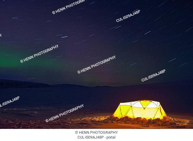Illuminated tent and northern lights in clear sky, Langjokull, South West Iceland