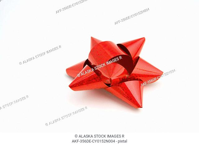 Closeup of one bright red Christmas gift bow on white background studio portrait